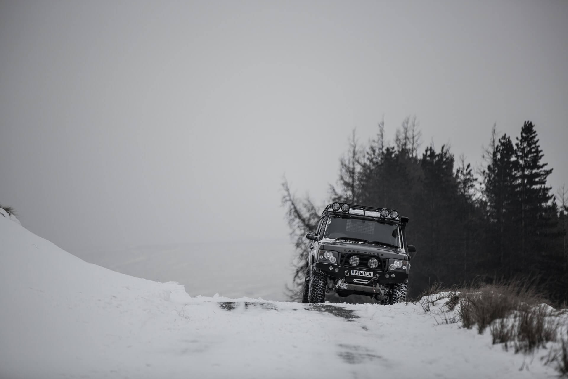 Black SUV in snowy terrain.