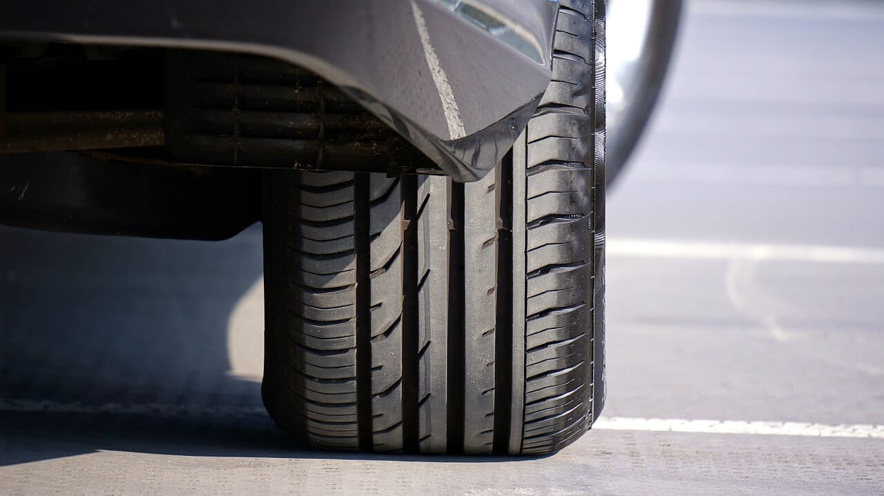 zoom-in on a black car tire rolling on paved road