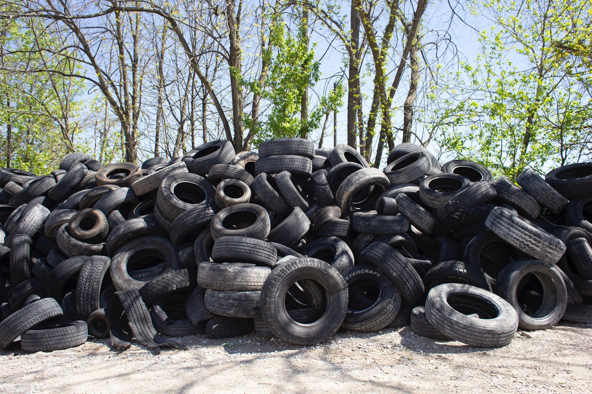 A messy pile of tires by some trees