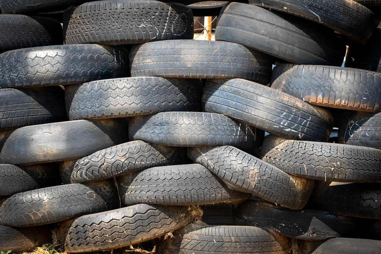 Dirty tires piled up in a criss-cross pattern