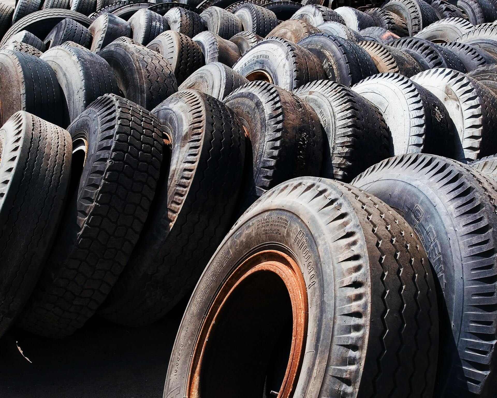 Rows of tires lined up side by side and leaning against each other